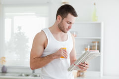 Man drinking orange juice while reading the news Royalty Free Stock Photography