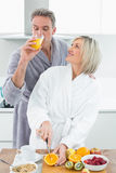 Man drinking orange juice and woman cutting fruits in  kitchen Royalty Free Stock Photography