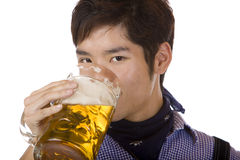 Man drinking out of Oktoberfest beer stein (Mass). Closeup of handsome young man drinking beer out of beer stein. Isolated on white Stock Images