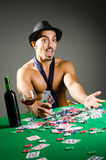Man drinking and playing in casino Stock Image