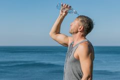 A man drinking and pours water on his face from bottle on the ocean, refreshing after a workout stock images