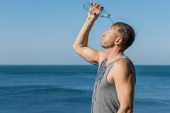 A man drinking and pours water on his face from bottle on the ocean, refreshing after a workout stock image
