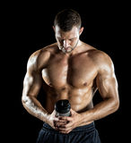 Man drinking protein shake. Young adult man drinking protein shake in gym. Black background Stock Photo