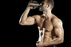 Man drinking protein shake. Young adult man drinking protein shake in gym. Black background stock photos