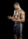 Man drinking protein shake. Young adult man drinking protein shake in gym. Black background royalty free stock image