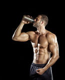 Man drinking protein shake. Young adult man drinking protein shake in gym. Black background stock images