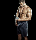 Man drinking protein shake. Young adult man drinking protein shake in gym. Black background royalty free stock photo