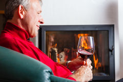 Man drinking red wine on fireplace Royalty Free Stock Photography