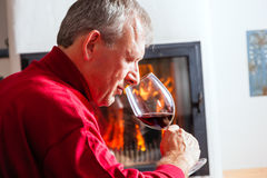 Man drinking red wine on fireplace Royalty Free Stock Photos
