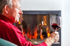Man drinking red wine on fireplace Royalty Free Stock Image