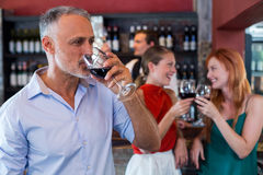 Man drinking red wine while two friends toasting the glasses in background Royalty Free Stock Photos