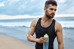 Man Drinking Refreshing Water After Workout At Beach. Drink Royalty Free Stock Photos