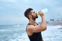 Man Drinking Refreshing Water After Workout At Beach. Drink Royalty Free Stock Photography