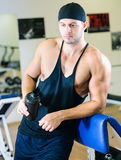 Man drinking shake in gym. Young adult man is working out an gym and drinking shake Stock Photography