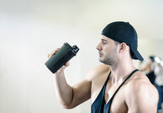 Man drinking shake in gym. Young adult man is working out an gym and drinking shake Stock Images