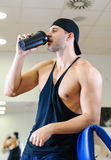 Man drinking shake in gym. Young adult man is working out an gym and drinking shake Royalty Free Stock Images