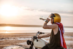 Man in drinking while sitting on his motocycle Stock Photography
