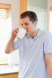 Man drinking some coffee out of his cup. Man drinking some coffee out of his white cup Royalty Free Stock Photos