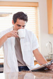 Man drinking some coffee while reading the newspaper Royalty Free Stock Image