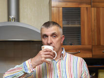 Man Drinking Tea. Or coffee in a kitchen, selective focus indoor shot Royalty Free Stock Photography