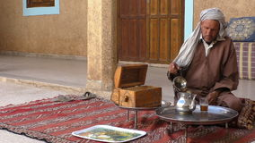 Man drinking tea at home in Morocco. TIOUT OR TIOUTE, TAROUDANT PROVINCE, MOROCCO, AFRICA - MARCH, 2016: Inside of an old Moroccan house. Berber man wearing stock video