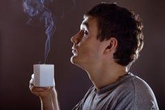 Man drinking warm beverage Royalty Free Stock Image