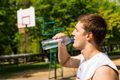 Man Drinking Water from Bottle on Basketball Court Royalty Free Stock Image