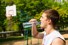 Man Drinking Water from Bottle on Basketball Court Stock Images