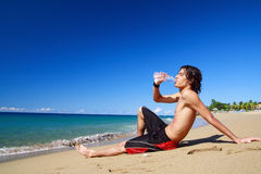 Man is drinking water from bottle on beach Royalty Free Stock Photography