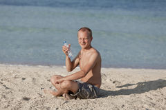 Man drinking water from a bottle on the beach portrait Stock Image