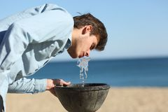 Man drinking water from a fountain on the beach royalty free stock photo