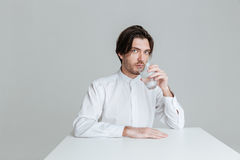 Man drinking from water glass while sitting at the table. Handsome young man drinking from water glass while sitting at the table isolated on the gray background stock photography