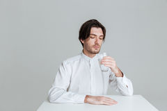 Man drinking from water glass while sitting at the table Royalty Free Stock Photos