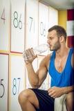 Man drinking water in locker room Royalty Free Stock Photo