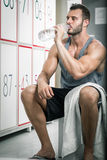 Man drinking water in locker room Royalty Free Stock Photography