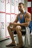 Man drinking water in locker room Royalty Free Stock Photos