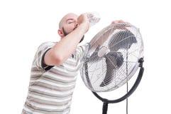 Man drinking water near blowing fan Stock Images