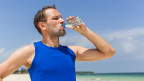 Man drinking water after running at beach. Thirsty sport runner Royalty Free Stock Images