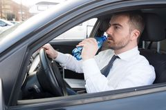 Man drinking water seated in car Stock Image