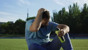 Man drinking water on stadium. Adult bearded man in sportswear drinking water from training bottle sitting on green stadium after workout stock video
