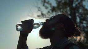 Man drinking water in sunlight stock video
