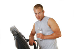 Man drinking water on a treadmill Royalty Free Stock Image