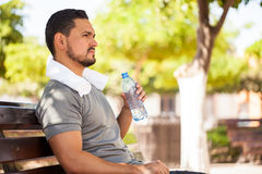 Man drinking water after working out. Closeup of a handsome young man drinking water from a bottle while taking a break from working out in a park Royalty Free Stock Photo