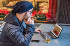 Man drinking whisky, smoking a cigar and looking at tablet Stock Photos