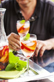 Man drinking white sangria. White sangria with fruits and berries Royalty Free Stock Images