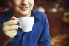Man drinking white tea cup in cafe Stock Image