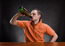 Man drinks alcohol over gray. Adult man drinks alcohol over gray Royalty Free Stock Images