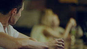 Man drinks alcohol. Young man at a bar counter drinks alcohol and looks at women in a bar stock video