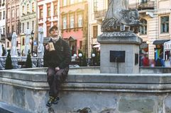 A man drinks beer from a wooden mug. Sitting near a fountain in the old city of Lviv Stock Image