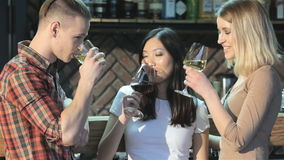 Man drinks beverages with two girls at the bar. Blond man drinking beverages with two pretty girls at the bar. Caucasian man drinking strong drink while two stock video footage